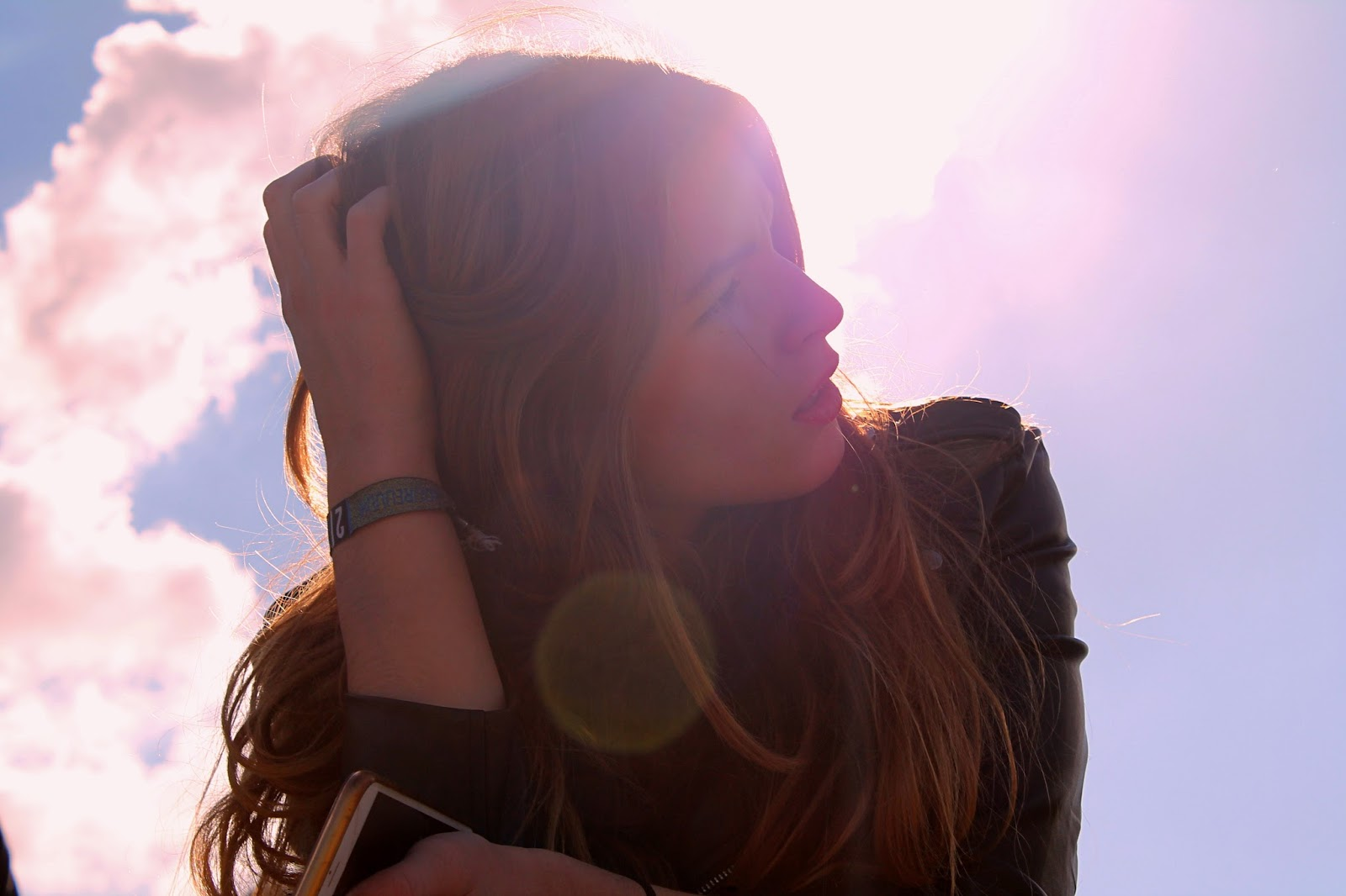 Woman playing with her hair whilst staring into the sun