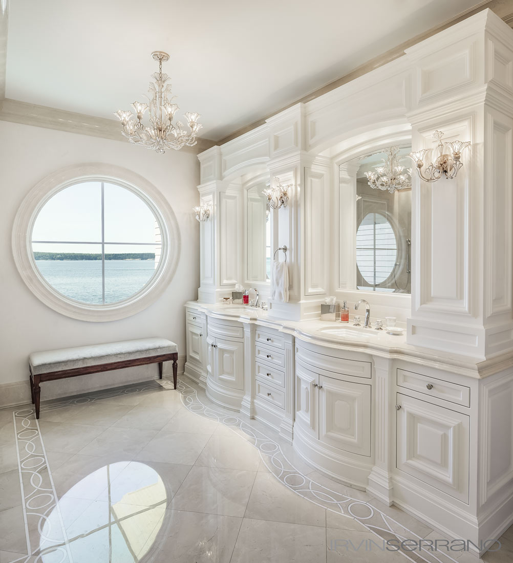 A master bathroom in a Southport Estate in coastal Maine features european style cabinets, designed by Urban Dwellings, and crema marfil marble.
