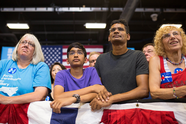 image of a teenage boy with his father, who appear to be ethnically Middle Eastern, at a Hillary rally