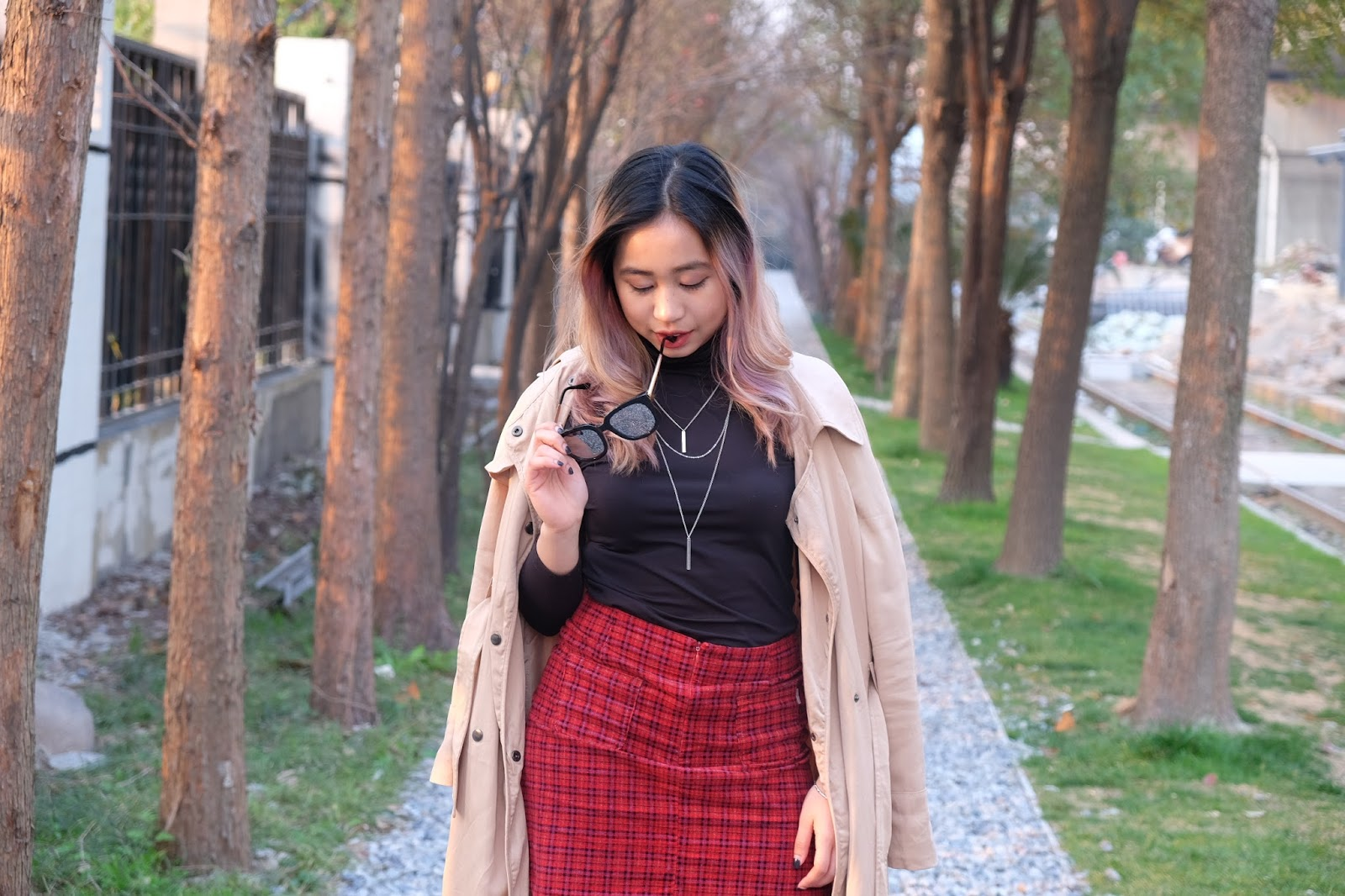 This is a photo of styling trench coat with plaid skirt and black turtleneck by Sidney Scarlett from www.sidneyscarlett.com