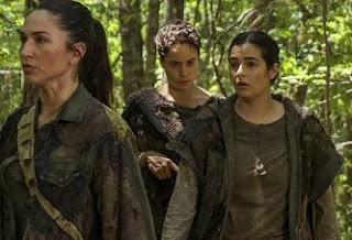 Imagem de Tara com integrantes da comunidade Oceanside Walking Dead no meio da floresta