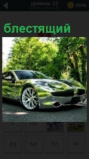 В свете солнечных лучей стоит на асфальте блестящий и переливающийся автомобиль