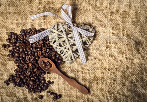 Pile of fresh coffee beans, heart and spoon