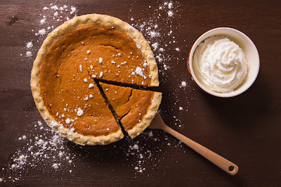 image of pumpkin pie with whipped cream and powdered sugar