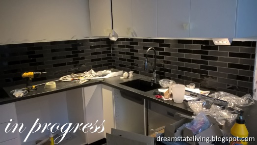 work in progress picture of kitchen renoovation, black tiles on the wall and upper cabinets in place