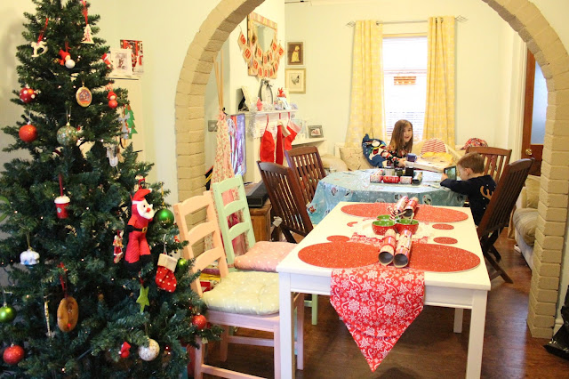 christmas day with two mismatching tables squeezed into small house