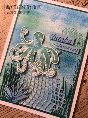 This image shows a hand made card against a wood grain background with an underwater scene and an octopus on the front, its sentiment reads 'thanks, you're one of a kind' and it is made with the Sea of Textures stamp set and the Under The Sea dies by Stampin' Up!