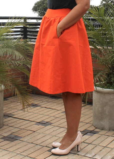 Side view of an orange faille skirt sewn from the Simplicity 1369 sewing pattern.