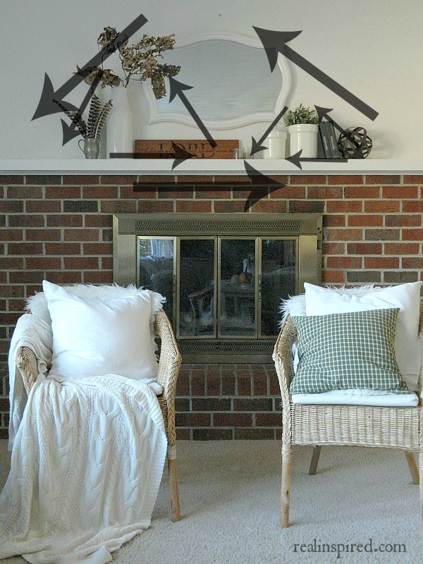 How to Decorate a Long Mantel using odd numbered groupings and triangles: arrows, bible verse, feathers, crocks, jars, plants, books, branch, fall, autumn, mirror, brick fireplace