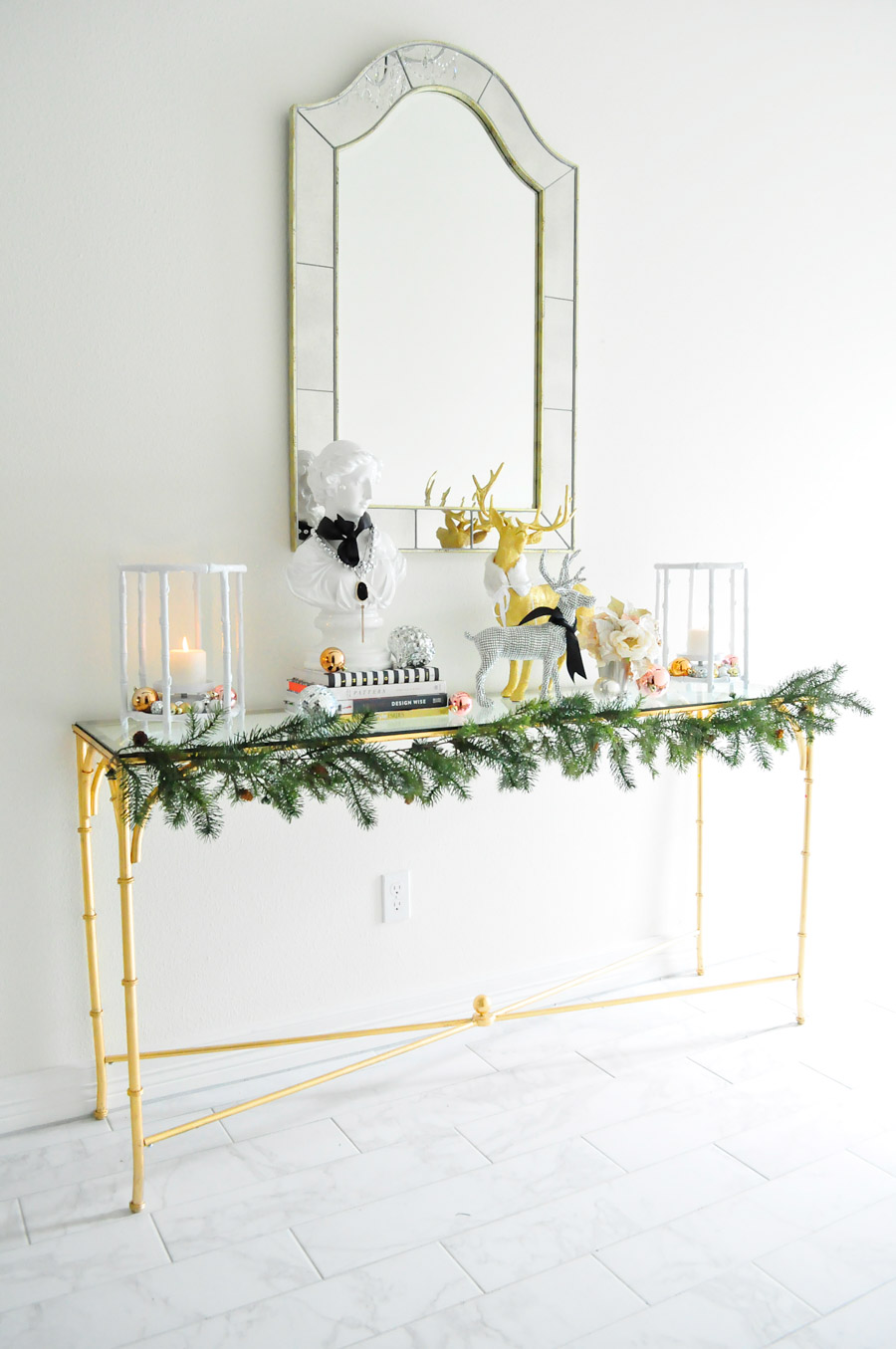 Gold bamboo console table adorned with holiday decor in blush, silver, gold and white. Chic and classic foyer with a black tray ceiling and tiled marble floors.