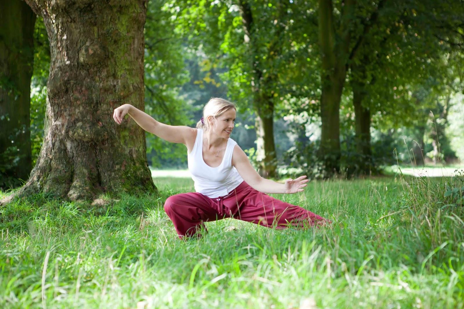 Person bei gymnastischer Übung auf Wiese in Park