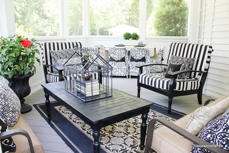This navy blue themed front porch decor looks stunning on this screened in porch. Love how the striped chair cushions compliment the carpet!