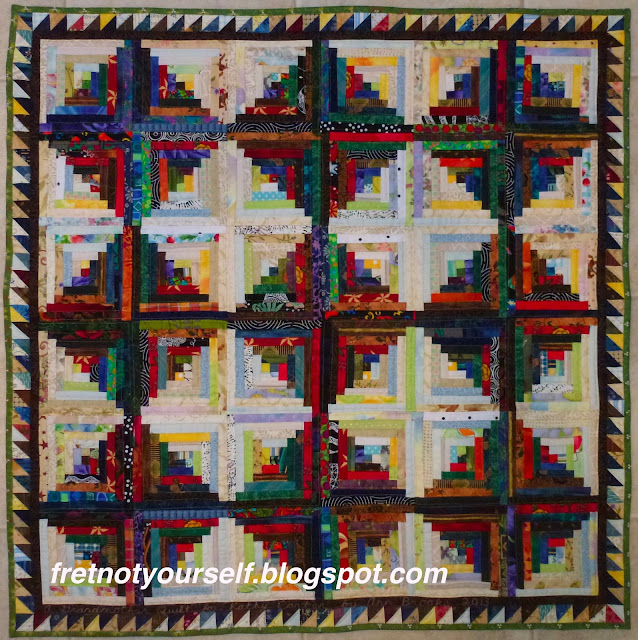 Log Cabin quilt with half-inch logs and a sawtooth border.
