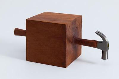 Escultura de un martillo atrapado en un cubo de madera.