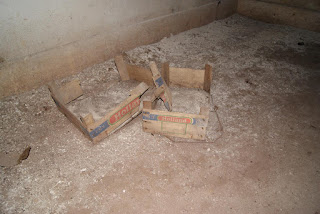 Auf dem Boden liegen alte Holzkisten, die zum Teil mit Schutt und Dreck gefüllt sind
