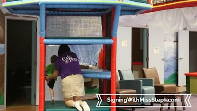 Cafe O'Play staff member helps child climb steps of two story play structure
