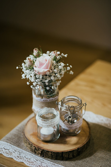 Wooden table, with a lace edged burlap table runner, with glass jars containing flowers and a tea light