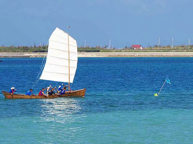white sail and team paddling sabani boat