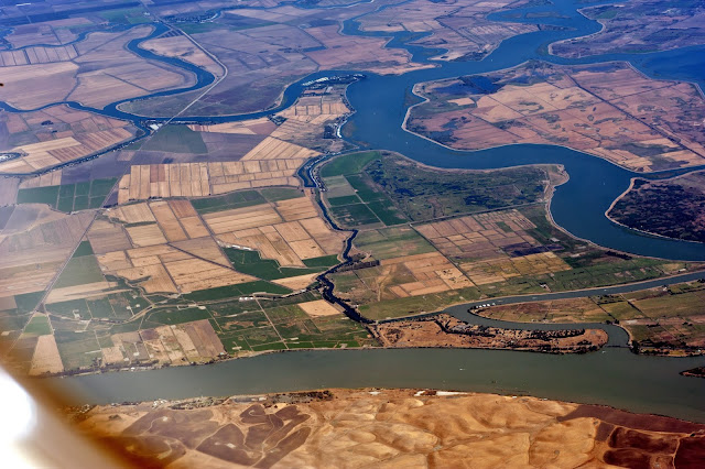 Aerial photo of farmlands, river/water channels and a bridge spanning the channel, located somewhere in the US.
