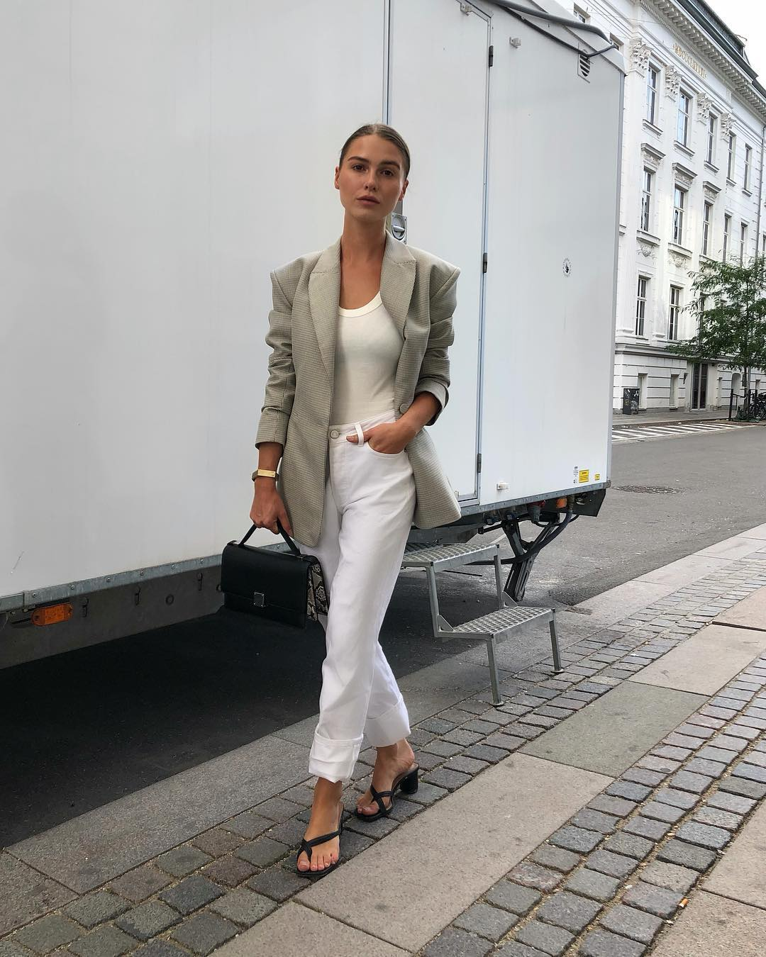 Spring and Summer Instagram Outfit Inspiration — Sophia Roe in a neutral blazer, beige tank top, white cuffed jeans, and black flip flip sandals