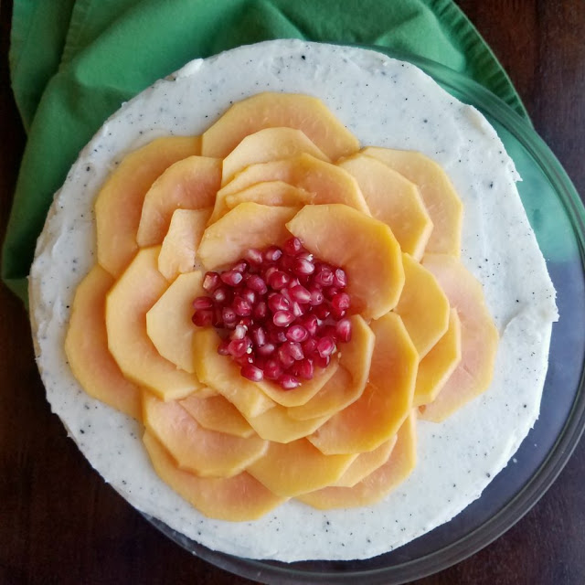 cake with white frosting specked with dragonfruit seeds and a papaya and pomegranate seed flower on top