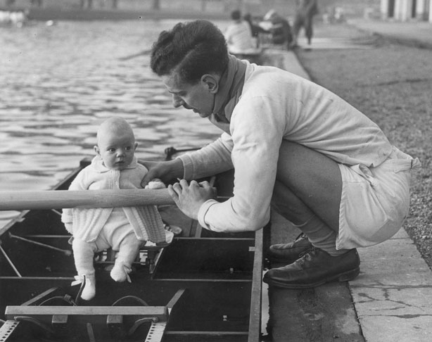 A member of the Cambridge University's rowing eight, balances his young son in the rowing boat. 1947-1948 Coxswain, rowing, and Other stories of Olympics. marchmatron.com