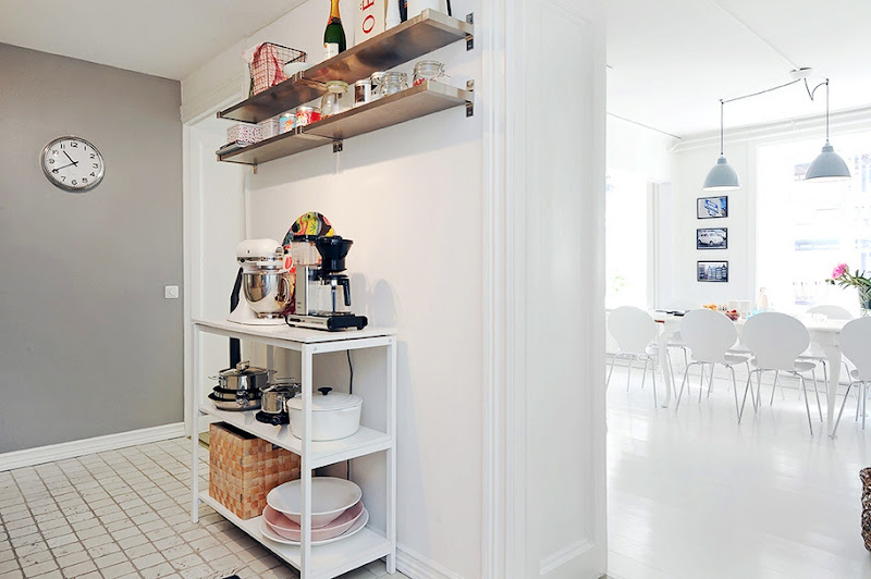 Small kitchen with floating shelves, grey walls, white tile floor and a view of the dining room
