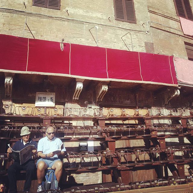 Two elderly many reading the newspaper whilst waiting for the Palio horse race in Siena