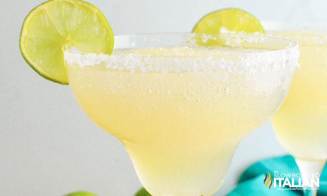 frozen margarita in glass garnished with slice of lime