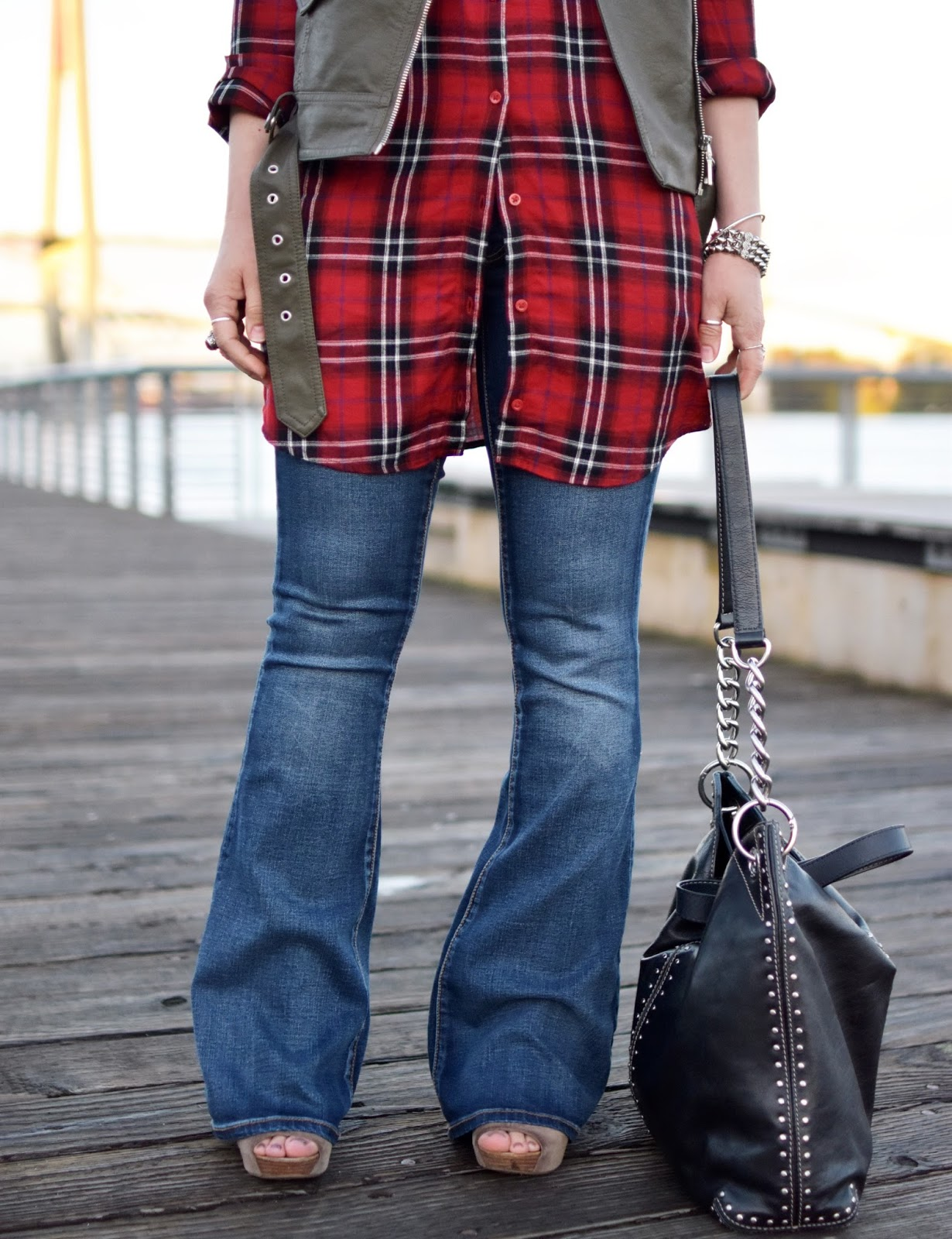 red plaid button-front tunic, flare jeans, olive moto vest, Michael Kors bag