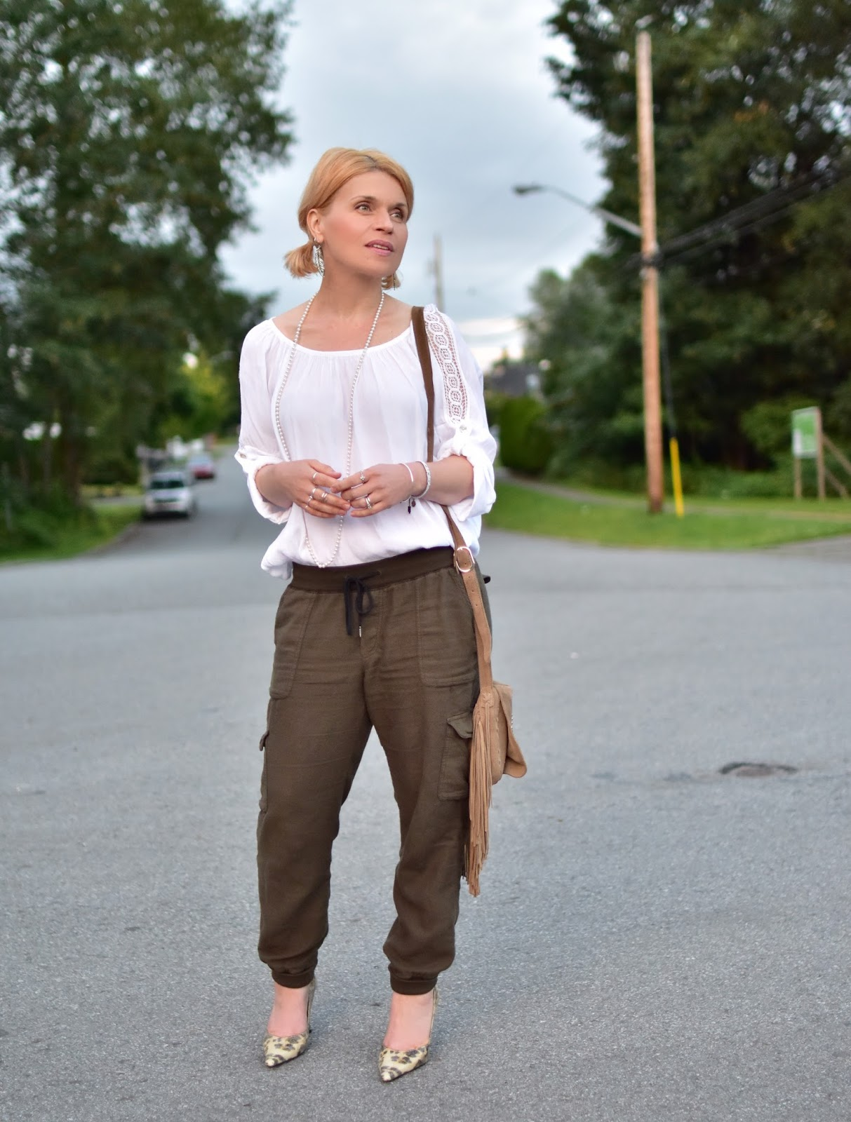 styling a scoop-necked peasant blouse with slouchy cargo pants, reptile pumps, and a fringy crossbody bag