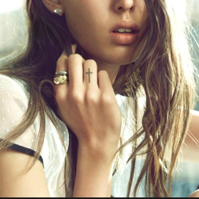 chica rubia, vemos su mano, lleva tatuaje de cruz en los dedos