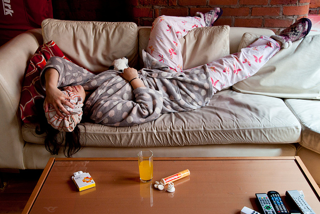 Photograph of woman lying on a couch with a hangover