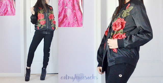 Rose embroidered floral applique bomber jacket from SheIn, worn with cutout joggers, a glitter mesh top, and a harness bodysuit.