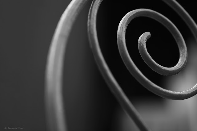 A Black and White Minimalist Photo of a Metal Spiral or a Fibonacci Spiral
