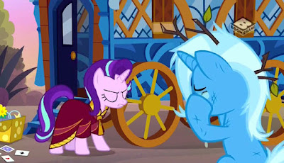 Starlight, wearing a red robe, confronts a crying Trixie in front of their wagon