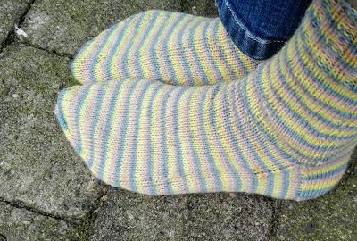 Zelfgebreide sokken in pastelkleuren: roze, geel, blauw.