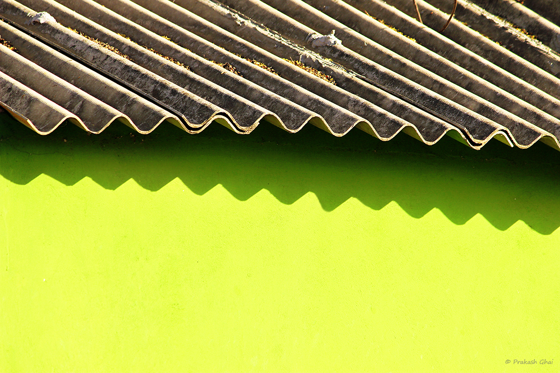 A Minimalist Photo of the green wall and wavy cement Roof of a kindergarten school in Bani Park Jaipur