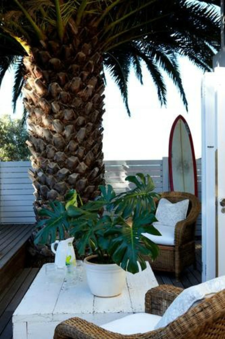 Coastal outdoor space with wicker club chairs and white sunbrella cushions