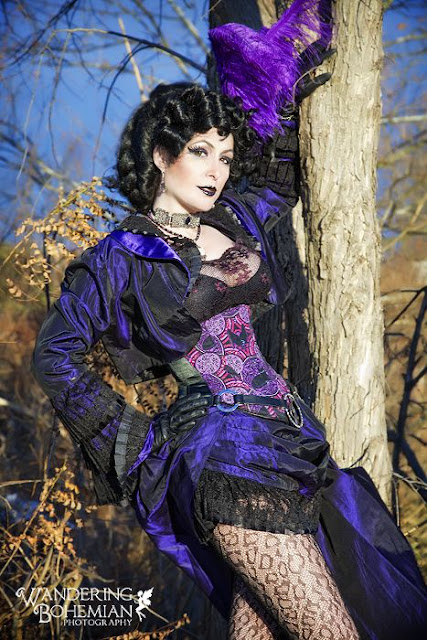Comic book cosplay for women. Steampunk fashion cosplay includes purple ostrich feathers in hair, purple corset and hi-low hem skirt, and peacock feathers.