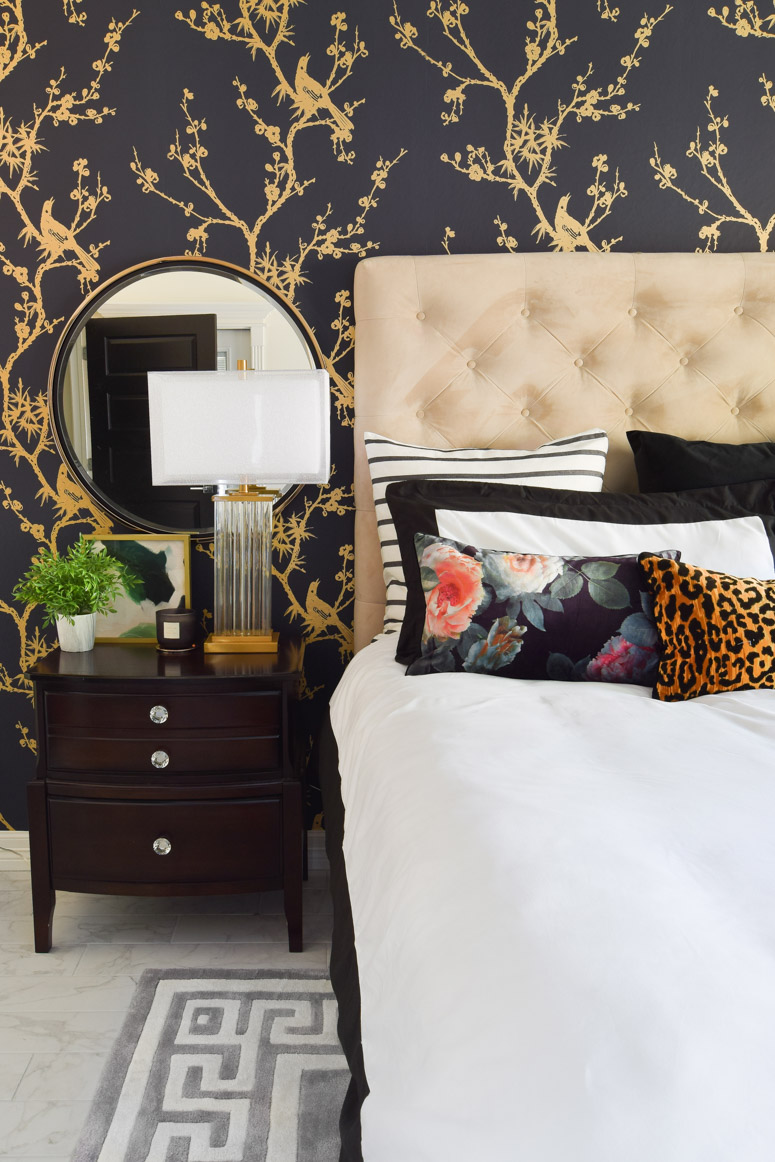 A big tufted headboard adorns this master bedroom makeover- I love the mirrors over the nighstands and all the gold accents.