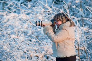 Photo of a female photographer taking pictures outside in the winter