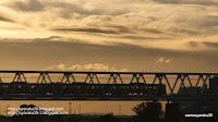 夕映えの多摩川の鉄橋を渡る電車写真