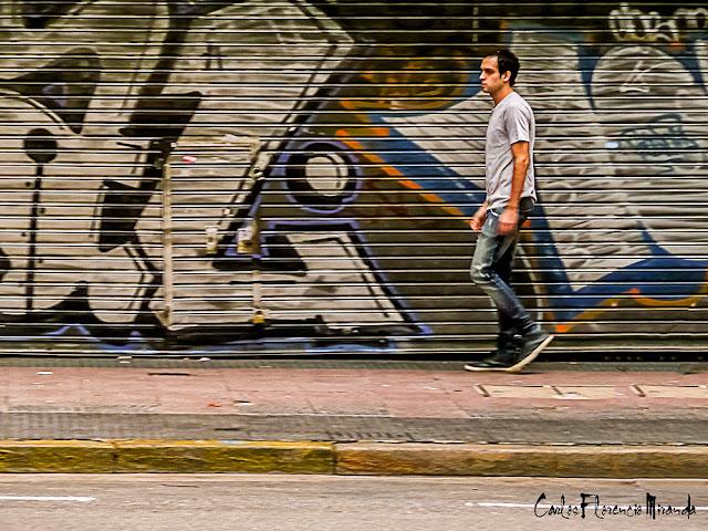 Un hombre pasa frente as un portón grafiteado