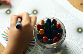 Image of Child drawing with crayons. Crayons in a jar