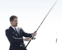 Foto de um executivo segurando uma vara de pesca de praia
