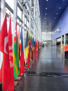 A photo looking down a long hallway with a glass wall to the left and a blue wall with a large entrance door to the right. In front of the glass wall is a long row of red, green, blue, and yellow flags hanging from short flagpoles resting on the floor.