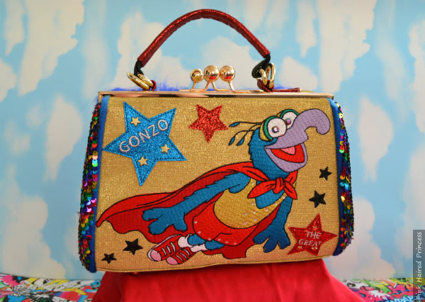 Irregular Choice Muppets Daredevil bag on red cape with cloudy background