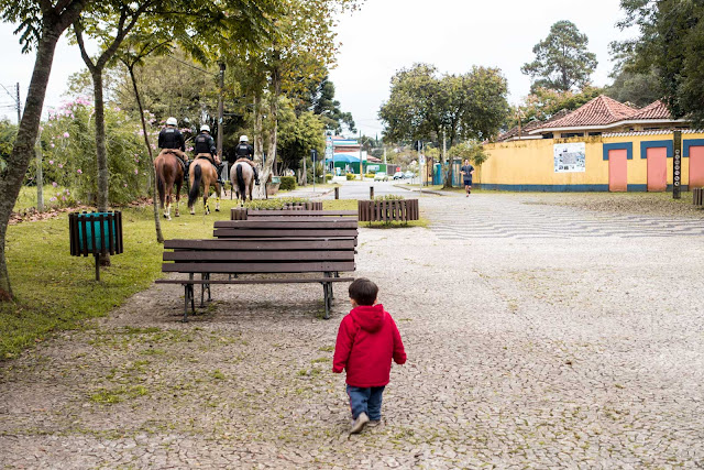 Criança correndo atrás de cavalos