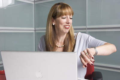 Woman at desk with laptop checking her watch
